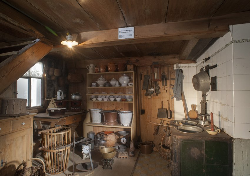 A kitchen from c.1870, plate rack, bench for pails of water, wood-fired stove